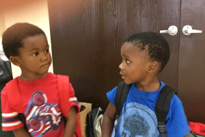 Kahron Wynn (red shirt), 3, and Jaiden Wallace, 4, look to reassure each other that school will be all right after getting backpacks stuffed with school items on Thursday, Aug. 17, at E.B. Jordan Homes. Kahron and Jaiden attend the Head Start program on Pine Street.