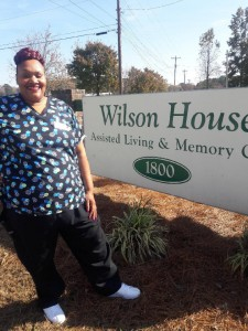 Ezrosta Faison stands in front of the sign for her employer Wilson House Assisted Living & Memory Center. Faison is a recent graduate of the Wilson Housing Authority's Family Self-Sufficiency program who has moved into her residence after going through five eye surgeries to allow her to regain her sight.