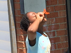 Aniyah Barnes of Whitfield Homes sends homemade dish soap and corn starch bubbles skyward through her just completed pipe cleaner bubble blower. Barnes, 10, created a variety of patterns to blow her sudsy concoction through as a camper at the Wilson Housing Authority's Arts Camps sponsored by the Arts Council of Wilson and the Wilson Rotary Club.